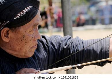 kulon progo,yogyakarta-october 20 2019: close up of old man holding arrow and bow,mataraman style