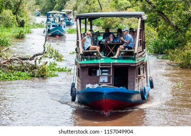 Kumai, Kalimantan/ Indonesia - November 25 2013: Visitors to Tanjung Puting National Park must travel the upper reaches of the river in traditional klotoks. They offer shade, and good wildlife viewing