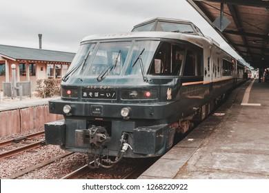 "Kumamoto, Japan - January 3, 2016: Exterior of Aso Boy train with its mascot ""Aso Kuroemon"" on the side. The train is run by JR (Japan Railway) Kyushu Company, currently stop at Aso Station."
