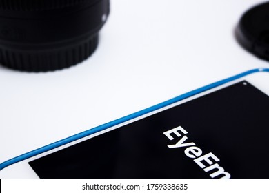 Kumamoto, Japan - Jun 18 2020 : The logo of Eyeem, a technology company with a global photography community and marketplace based in Berlin, on iPhone on white background with camera lens & its cap.