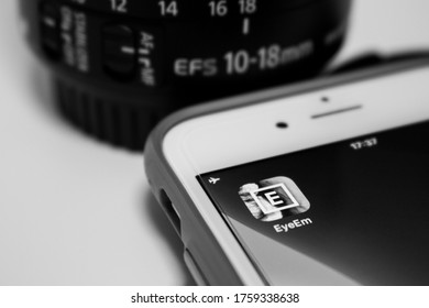 Kumamoto, Japan - Jun 18 2020 : The icon of Eyeem, a tech company with a global photography community & marketplace based in Berlin, on iPhone with camera lens & its cap in monochrome.