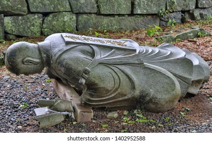 Kumamoto, Japan - May 13, 2018: Dropped down, fallen buddhist monk granite stone statuesque in a Temple in Japan. Higo Honmyo Temple.