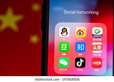 Kumamoto, JAPAN - Oct 3 2020 : China's Popular Social Media Icons (Tencent QQ, Sina Weibo, Tencent Video, Douban, Zhihu, Jinri Toutiao WeChat, TikTok, Xiao Hong Shu) on iPhone with Chinese flag