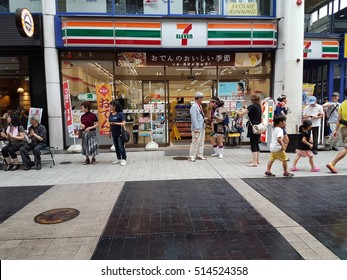 Kumamoto,Japan-September 18th,2016. People walk past 7-eleven convenience store in Kumamoto,Japan. 7-eleven is world's largest oerator, franchisor and licensor of convenience stores.