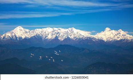 Kumaon Himalayan mountain range with view of flying migratory birds as viewed from Binsar zero point Uttarakhand India.