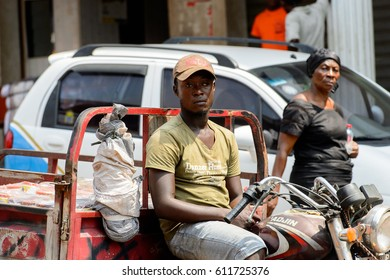 KUMASI, GHANA - JAN 15, 2017: Unidentified Ghanaian man rides a tricycle at the Kumasi market. Ghana people suffer of poverty due to the bad economy.