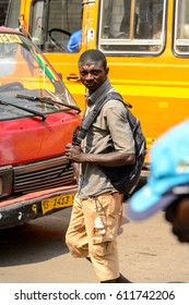 KUMASI, GHANA - JAN 15, 2017: Unidentified Ghanaian man walks with a backpack at the Kumasi market. Ghana people suffer of poverty due to the bad economy.