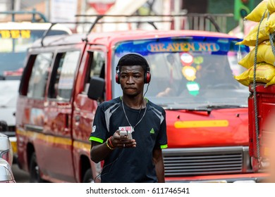 KUMASI, GHANA - JAN 15, 2017: Unidentified Ghanaian boy listens to music at the Kumasi market. Ghana people suffer of poverty due to the bad economy.