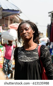 KUMASI, GHANA - JAN 15, 2017: Unidentified Ghanaian woman in black clothes smiles at the Kumasi market. Ghana people suffer of poverty due to the bad economy.