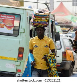 KUMASI, GHANA - JAN 15, 2017: Unidentified Ghanaian man carries clothes on his head at the Kumasi market. Ghana people suffer of poverty due to the bad economy.