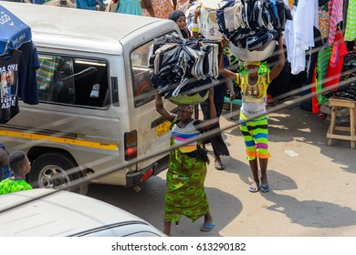 KUMASI, GHANA - JAN 15, 2017: Unidentified Ghanaian women carry basins with clothes at the Kumasi market. Ghana people suffer of poverty due to the bad economy.