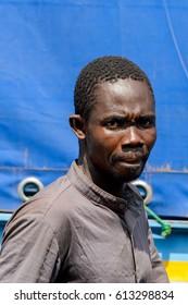 KUMASI, GHANA - JAN 15, 2017: Unidentified Ghanaian man walks at the Kumasi market. Ghana people suffer of poverty due to the bad economy.