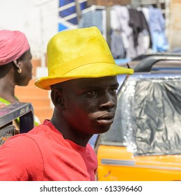 KUMASI, GHANA - JAN 15, 2017: Unidentified Ghanaian man in red shirt and yellow hat looks ahead at the Kumasi market. Ghana people suffer of poverty due to the bad economy.