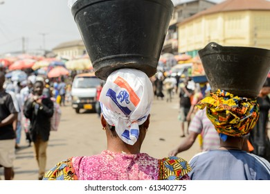 KUMASI, GHANA - JAN 15, 2017: Unidentified Ghanaian woman carries a basin on her head at the Kumasi market. Ghana people suffer of poverty due to the bad economy.