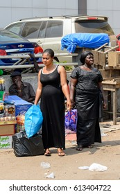 KUMASI, GHANA - JAN 15, 2017: Unidentified Ghanaian woman in black dress stands at the Kumasi market. Ghana people suffer of poverty due to the bad economy.
