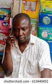 KUMASI, GHANA - JAN 15, 2017: Unidentified Ghanaian man talks on the cellphone at the Kumasi market. Ghana people suffer of poverty due to the bad economy.