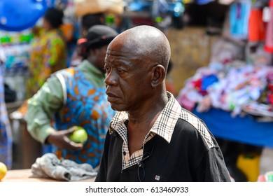 KUMASI, GHANA - JAN 15, 2017: Unidentified Ghanaian old man looks ahead at the Kumasi market. Ghana people suffer of poverty due to the bad economy.