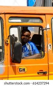KUMASI, GHANA - JAN 15, 2017: Unidentified Ghanaian man drives an orange car at the Kumasi market. Ghana people suffer of poverty due to the bad economy.