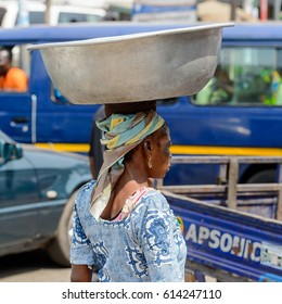 KUMASI, GHANA - JAN 15, 2017: Unidentified Ghanaian woman carries a basin at the Kumasi market. Ghana people suffer of poverty due to the bad economy.