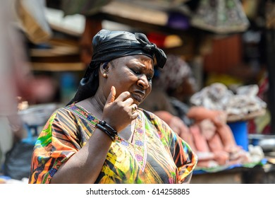KUMASI, GHANA - JAN 15, 2017: Unidentified Ghanaian woman in colored shirt and black headscarf looks down at the Kumasi market. Ghana people suffer of poverty due to the bad economy.