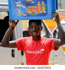 KUMASI, GHANA - JAN 15, 2017: Unidentified Ghanaian man in red shirt carries a box at the Kumasi market. Ghana people suffer of poverty due to the bad economy.