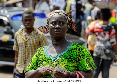 KUMASI, GHANA - JAN 15, 2017: Unidentified Ghanaian woman in green dress holds money at the Kumasi market. Ghana people suffer of poverty due to the bad economy.