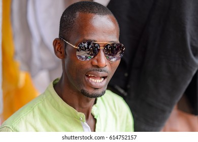 KUMASI, GHANA - JAN 15, 2017: Unidentified Ghanaian man in sunglasses opens his mouth at the Kumasi market. Ghana people suffer of poverty due to the bad economy.