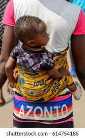KUMASI, GHANA - JAN 15, 2017: Unidentified Ghanaian little girl is carried by her mother at the Kumasi market. Ghana children suffer of poverty due to the bad economy.