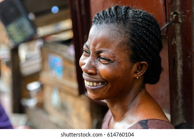 KUMASI, GHANA - JAN 15, 2017: Unidentified Ghanaian woman with braids smiles at the Kumasi market. Ghana people suffer of poverty due to the bad economy.