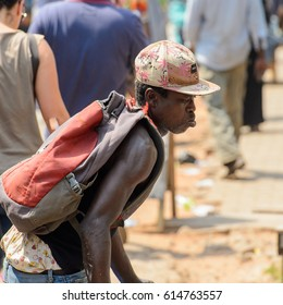 KUMASI, GHANA - JAN 15, 2017: Unidentified Ghanaian man in a cap and backpack at the Kumasi market. Ghana people suffer of poverty due to the bad economy.