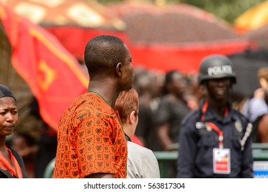 KUMASI, GHANA - JAN 16, 2017: Unidentified Ghanaian man in orange clothes at the memorial ceremony dedicated to the Queen mother of the Asante kingdom, who died on Nov 14, 2016 at the age of 111