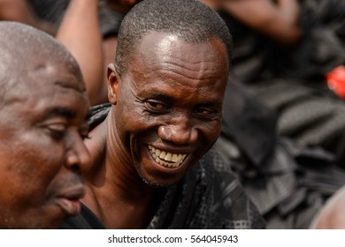 KUMASI, GHANA - JAN 16, 2017: Unidentified Ghanaian man in black clothes smiles at the memorial ceremony dedicated to the Queen mother of the Asante kingdom, who died on Nov 14, 2016 at the age of 111
