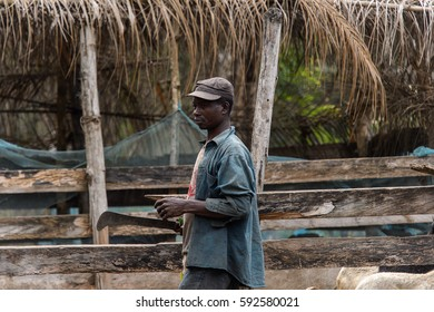 KUMASI, GHANA - Jan 16, 2017: Unidentified Ghanaian man in dirty clothes holds machete in his hand. People of Ghana suffer of poverty due to the bad economy