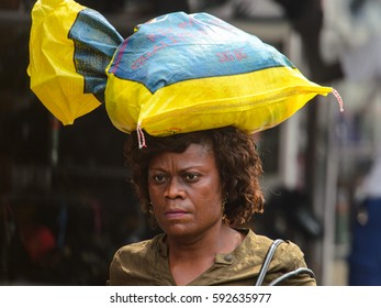 KUMASI, GHANA - Jan 16, 2017: Unidentified Ghanaian woman carries a plastic bag on her head. People of Ghana suffer  poverty due to the bad economy