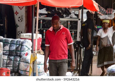 KUMASI, GHANA - Jan 16, 2017: Unidentified Ghanaian man in red shirt walks along the market. People of Ghana suffer  poverty due to the bad economy