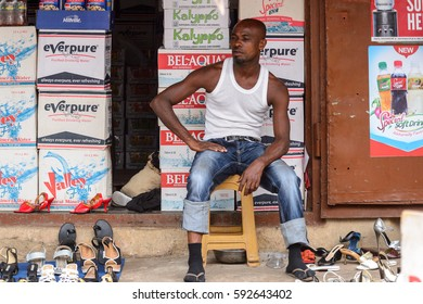 KUMASI, GHANA - Jan 16, 2017: Unidentified Ghanaian man sits on plastic chair on the street. People of Ghana suffer  poverty due to the bad economy