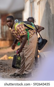 KUMASI, GHANA - Jan 16, 2017: Unidentified Ghanaian boy with backpack and in plaid shirt bends down. People of Ghana suffer  poverty due to the bad economy