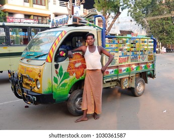 Kumbakonam, India - November, 23rd, 2017. Truck driver and his colorful handpainted vehicle on the street of Kumbakonam, Tamil Nadu, India.