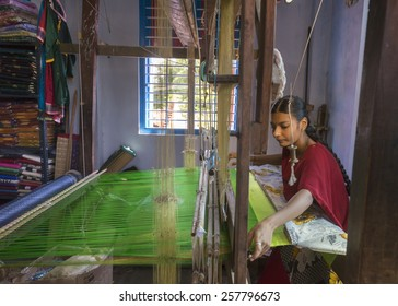 KUMBAKONAM, INDIA - OCTOBER 11, 2013: Home silk sari weaving on a hand loom set in a small room. The young woman works on a green piece of textile.