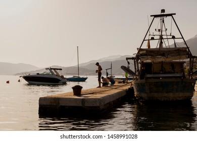 Kumbor,Monte Negro ,july 3,2019 Men fishing on the sea docks in sunset,big boat behind them