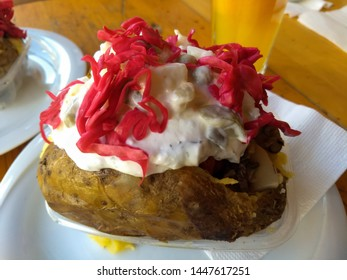kumpir is stuffed roasted potato with butter, cheddar cheese, boiled bulgur salad, boiled corn, olives, russian salad, ketchup, mayonnaise, red cabbage, mushrooms