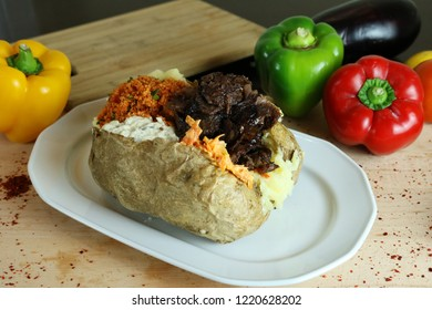 Kumpir - Traditional Turkish meal with baked potato, butter, cheese, bulgur salad, kebab meat and hot spices