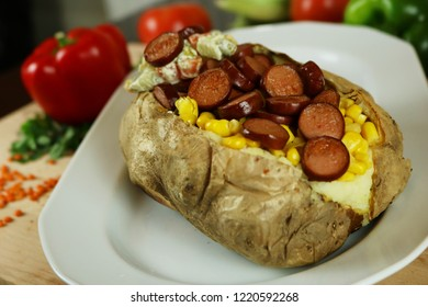 Kumpir - Turkish baked potato with butter, cheese, corn, beef sausage, vegetable salad and spices. This kumpir is traditional turkish food isolated on white background
