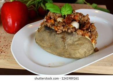 Kumpir - Turkish baked potato with butter, cheese, minced beef meat, mozzarella, and tomato sauce with basil. This kumpir is traditional turkish food isolated on white background
