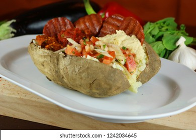 Kumpir - Turkish baked potato with butter, cheese, beef sausage, vegetable salad and spices. This kumpir is traditional turkish food isolated on white background