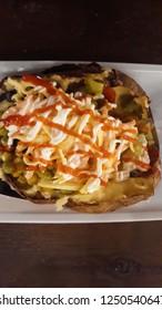 Kumpir, Turkish baked potato with cheese, corn, sausage, ketchup, mayonnaise and olives.
