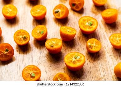 Kumquat fruit slices on a cutting board flat lay