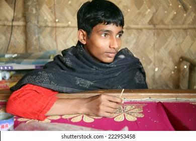 KUMROKHALI, INDIA - JAN 16: Anandalok Naskar working on the decoration of textiles in Kumrokhali, India on Jan 16, 2009.