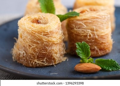 Kunafa, traditional arabic sweets in blue ceramic plate on a gray concrete background. side view, close up, selective focus.