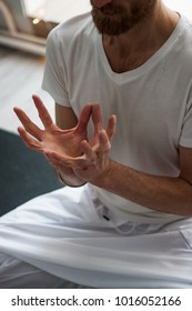 Kundalini yoga. Man holding mudra (special hands position) and wearing white clothes. Doing asana and mailtaining balance inside.